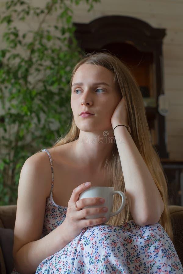 L'ado de femme détendent la tasse à l'intérieur photo libre de droits