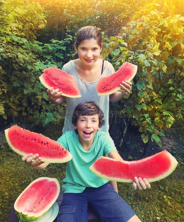 L'ado de garçon et de fille ont l'amusement mangeant la pastèque photo libre de droits
