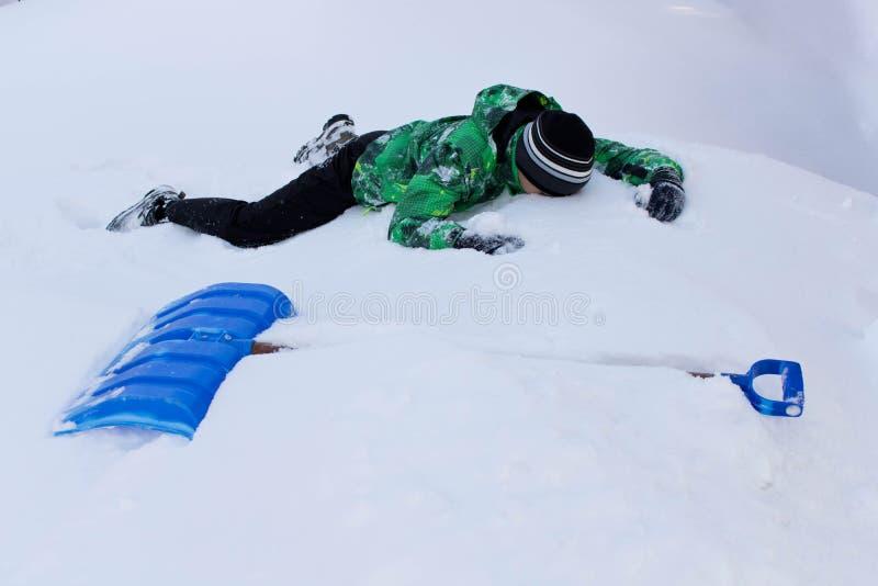 L'ado nettoie la pelle à neige Nettoyage de neige dans la cour image stock