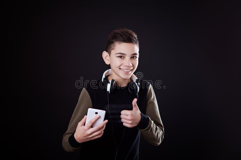 L'adolescent écoute la musique sur un fond noir images stock