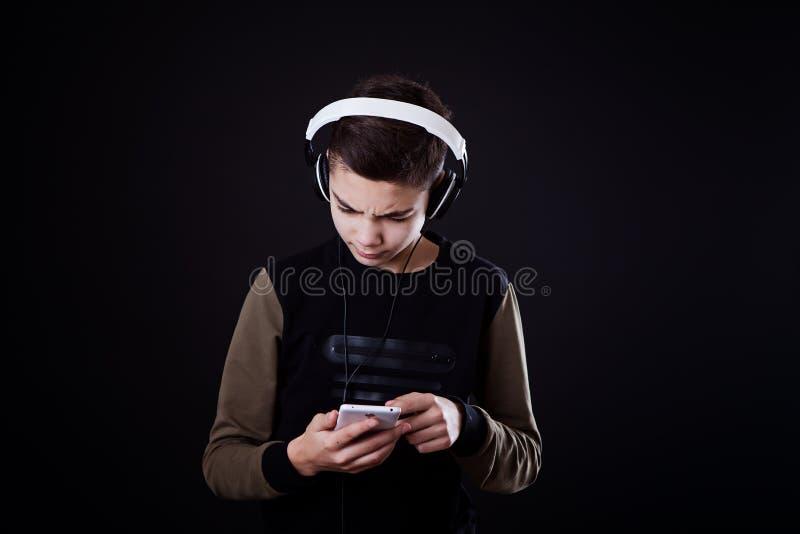 L'adolescent écoute la musique sur un fond noir photos stock