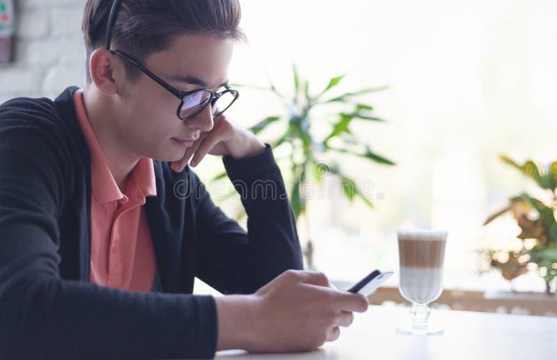L'adolescent asiatique mignon en verres 15-16 années s'assied avec un téléphone dans un café, éducation en ligne photographie stock libre de droits
