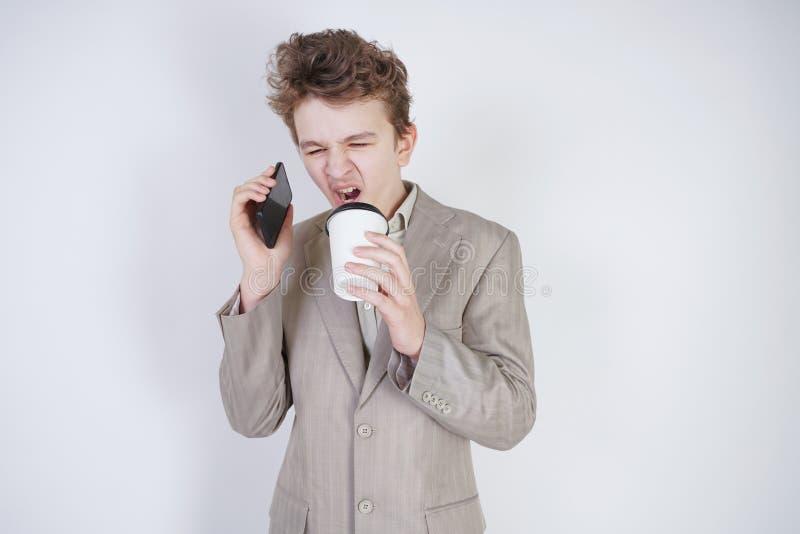 L'adolescent caucasien dans un costume gris se tient avec un t?l?phone portable et une tasse de caf? de papier sur un fond blanc  photographie stock libre de droits
