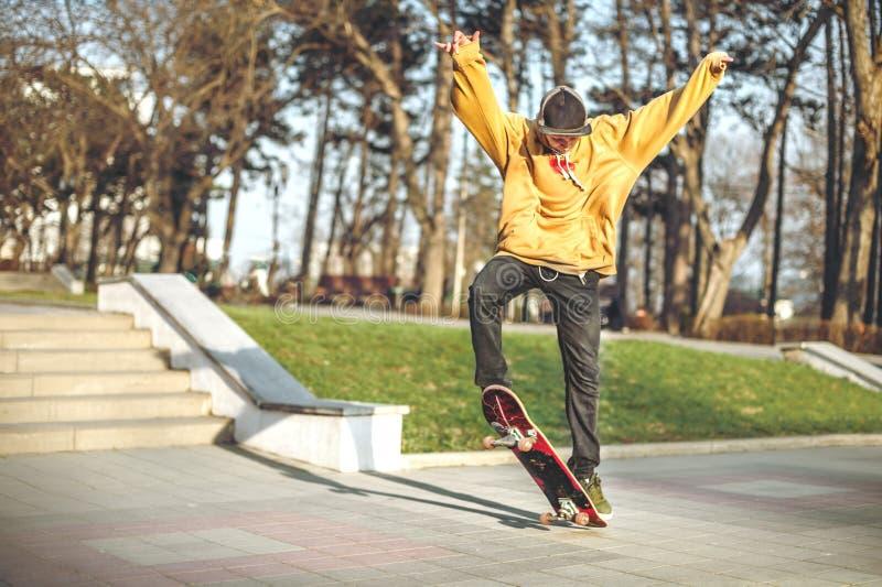 L'adolescent dans un pull molletonné et un chapeau saute avec un conseil dans la ville contre le contexte de la lumière urbaine d images libres de droits