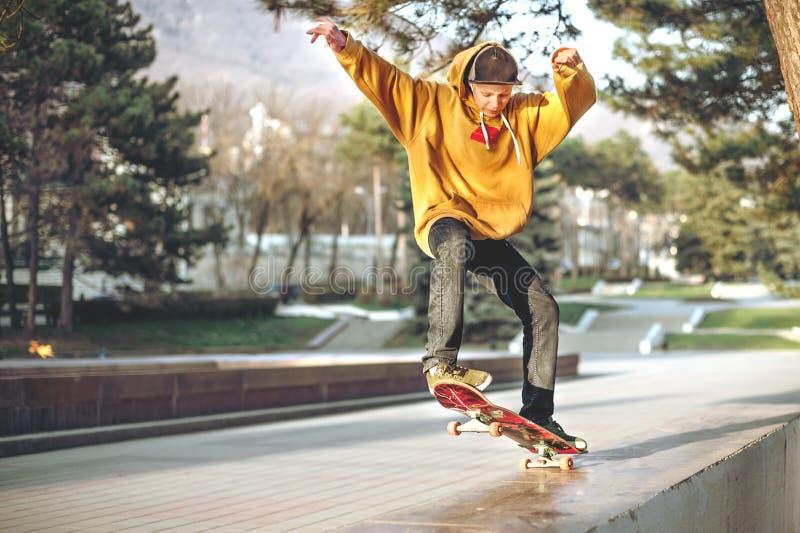 L'adolescent dans un pull molletonné et un chapeau saute avec un conseil dans la ville contre le contexte de la lumière urbaine d photos stock