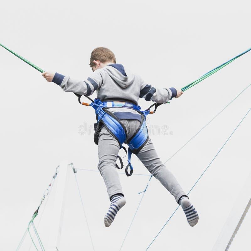 L'adolescent de garçon saute haut au ciel assuré avec des brides sur un oto-rhino image libre de droits