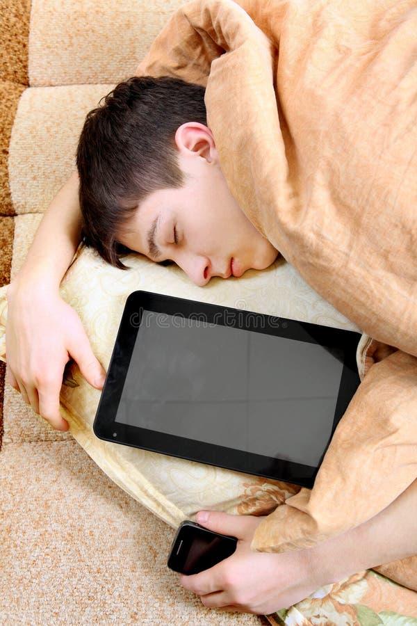 L'adolescent dort avec la tablette images stock