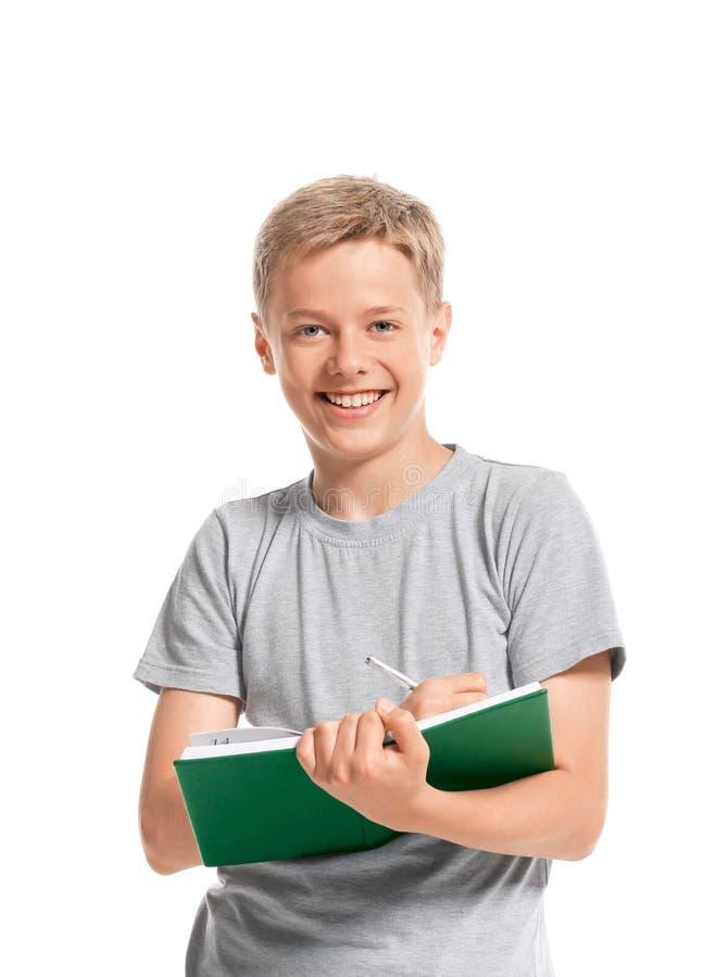 L'adolescent heureux écrit quelque chose dans un carnet photo libre de droits