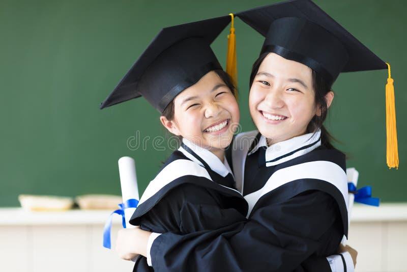 L'adolescent heureux dans l'obtention du diplôme habille étreindre et sourire photo libre de droits