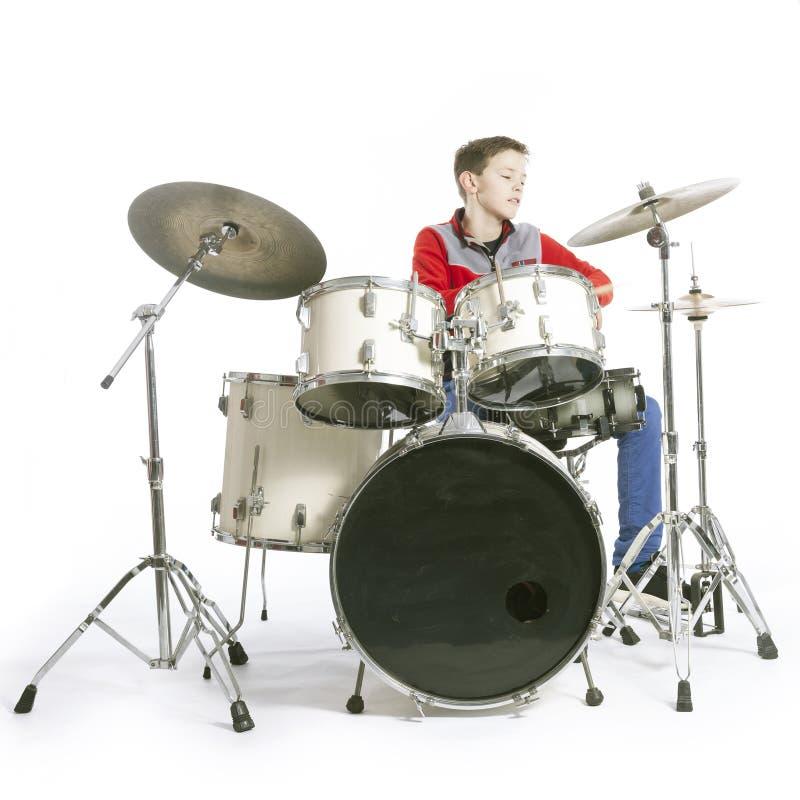 L'adolescent joue des tambours dans le studio avec le fond blanc photographie stock