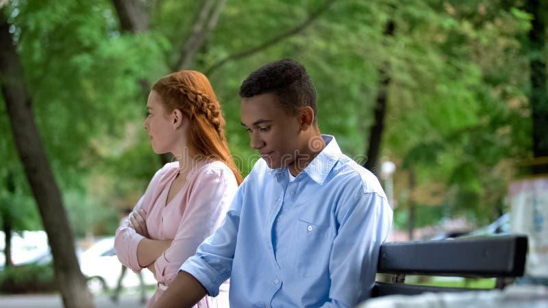 L'adolescent offensé petite amie et petit ami assis séparément sur le banc dans le parc photo libre de droits