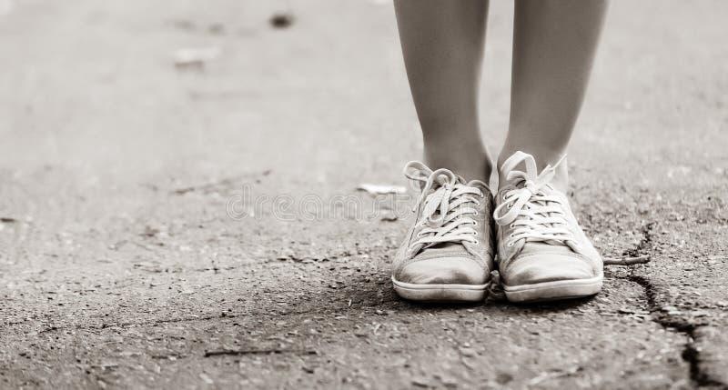 L'adolescent paye dans des chaussures en caoutchouc en parc photo stock