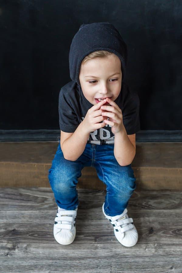 L'adolescent positif dans le chapeau noir s'assied à l'intérieur photographie stock libre de droits