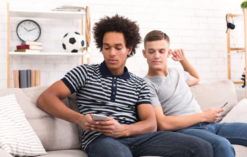 L'adolescent remarquant aux amis téléphonent à la maison photographie stock