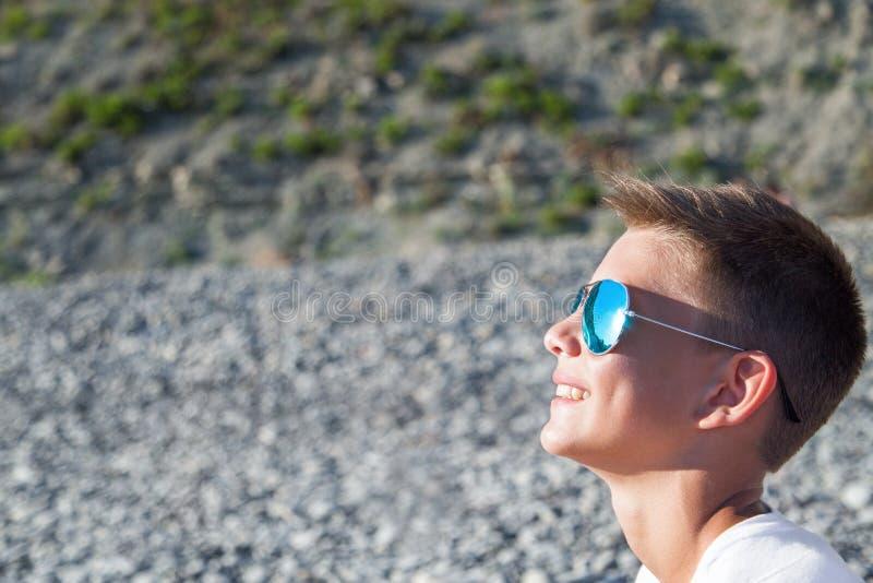 L'adolescent s'assied sur la plage image libre de droits