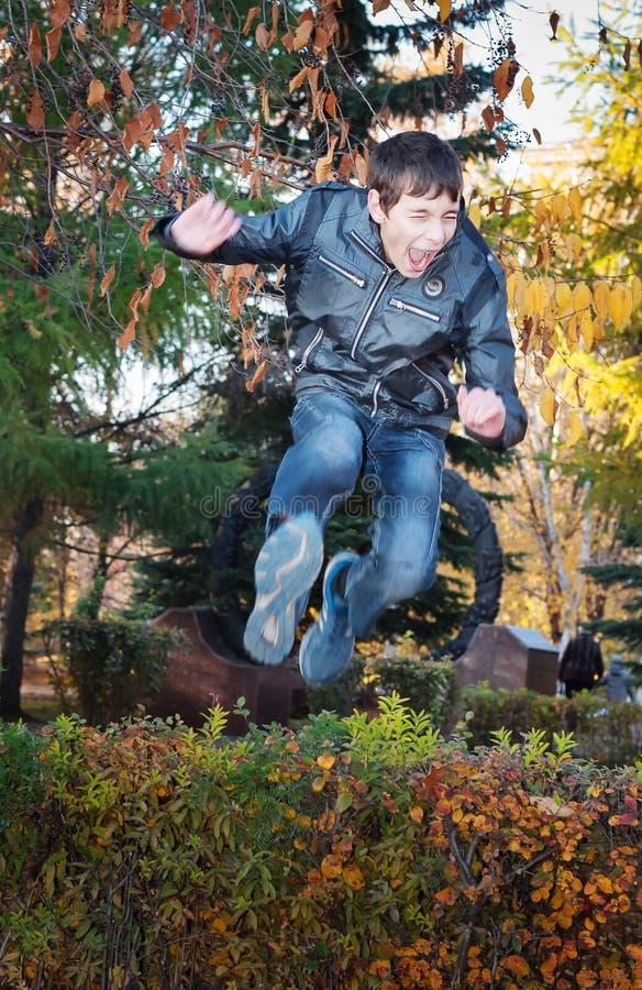 L'adolescent saute par-dessus des buissons photo stock