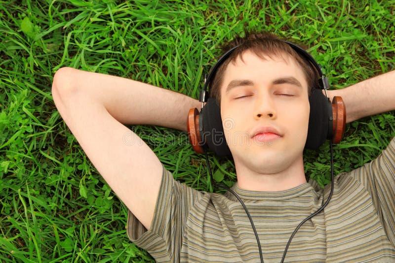 L'adolescent se trouve sur l'herbe dans des écouteurs photos libres de droits