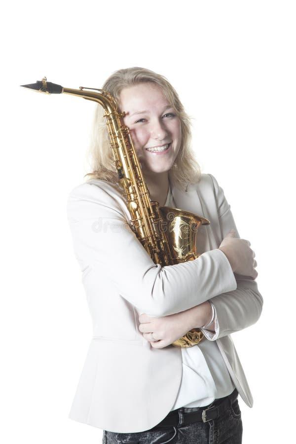L'adolescente étreint le saxophone dans le studio avec le fond blanc photographie stock libre de droits