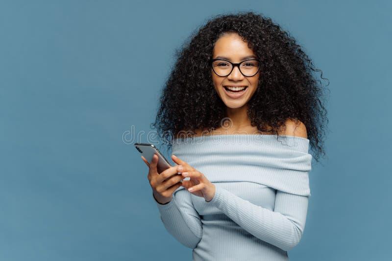 L'adolescente adorabile gode della comunicazione online, tiene il telefono cellulare moderno, controlli invia con la posta elettr fotografia stock
