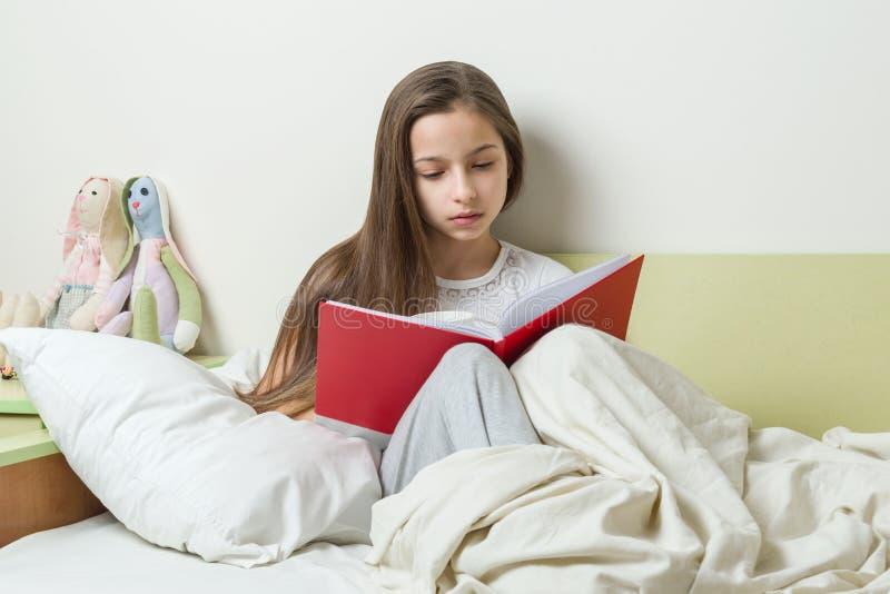 L'adolescente 10 anni legge un taccuino della scuola sul letto Interno del fondo della stanza del ` s dei bambini fotografia stock libera da diritti