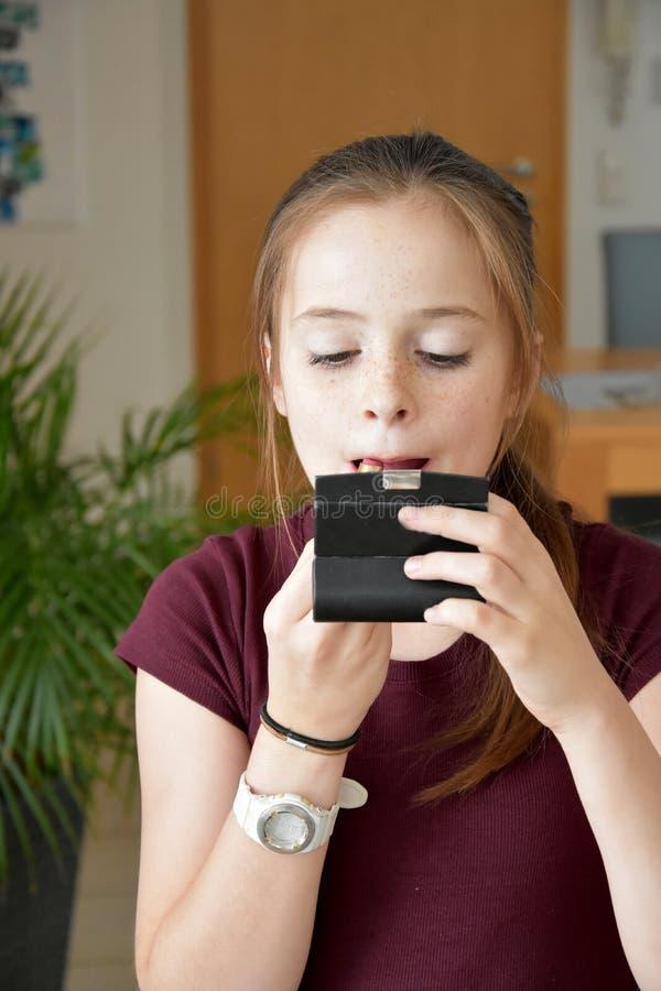 L'adolescente applica il rossetto fotografia stock libera da diritti