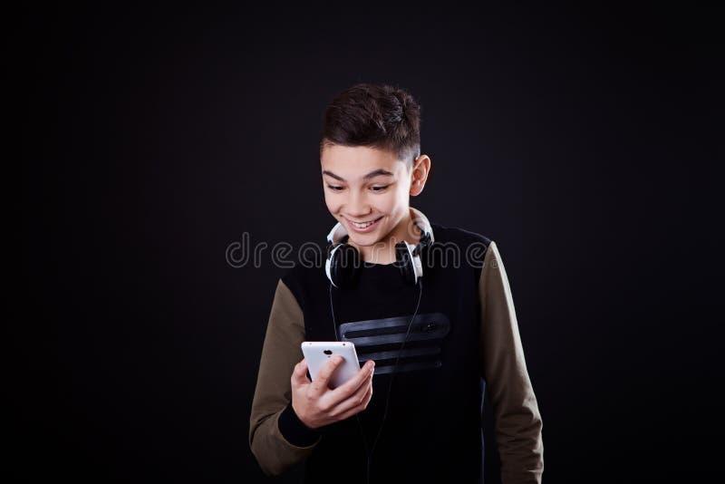 L'adolescente ascolta musica su un fondo nero immagine stock libera da diritti