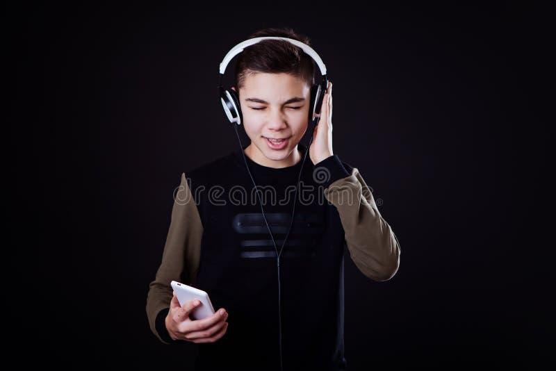 L'adolescente ascolta musica su un fondo nero fotografia stock libera da diritti