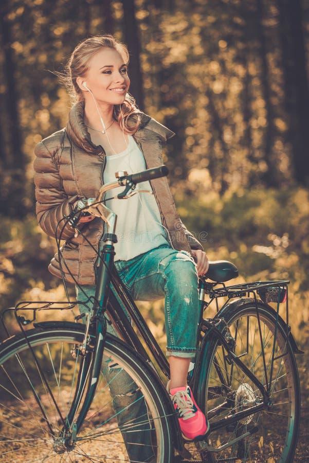 L'adolescente ascolta musica su una bicicletta all'aperto fotografie stock libere da diritti