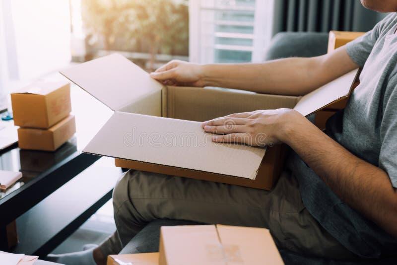 L'adolescente asiatico dell'imprenditore sta aprendo una scatola di cartone per mettere il prodotto che il cliente ha ordinato ne immagine stock