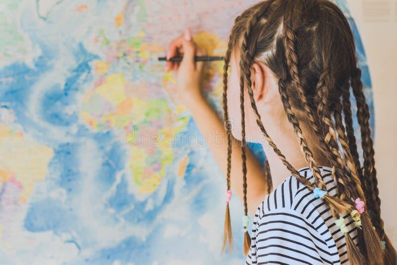 L'adolescente avec des tresses fait des marques de crayon sur la carte du monde photo libre de droits