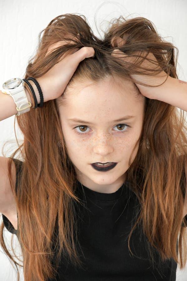 L'adolescente avec les lèvres noires ébouriffe ses cheveux image libre de droits