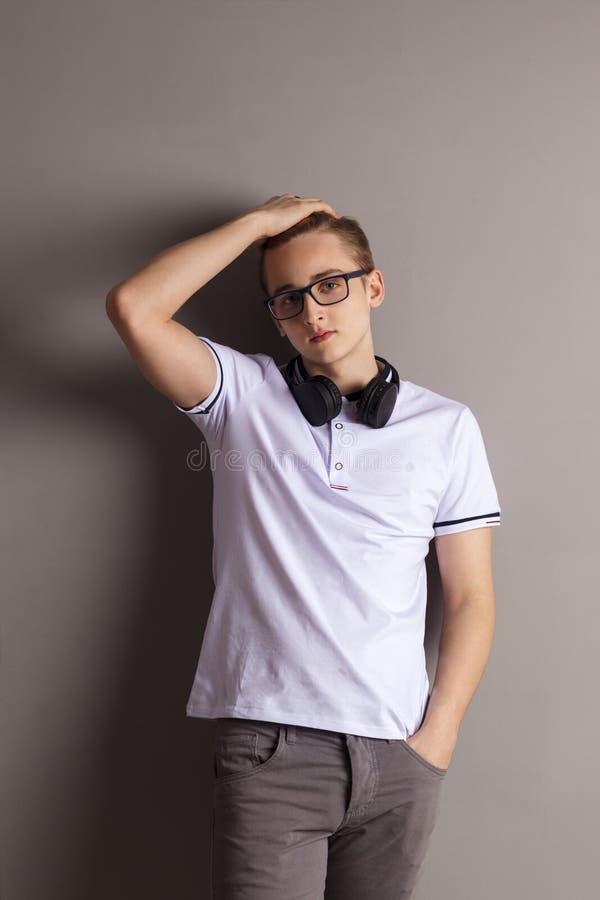 L'adolescente bello del ragazzo con le cuffie sta la parete vicina fotografie stock libere da diritti