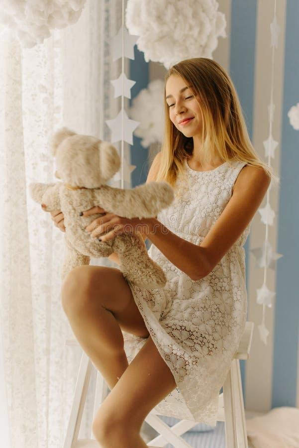 L'adolescente blonde de sourire tient l'ours de nounours tout en se reposant sur la chaise images libres de droits