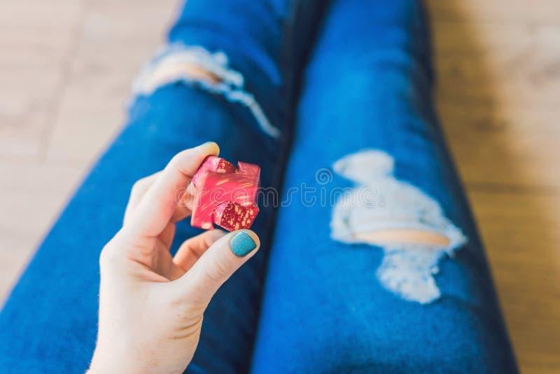 L'adolescente de fille dans des jeans troués se tient dans des mains et joue avec le spinn photo libre de droits