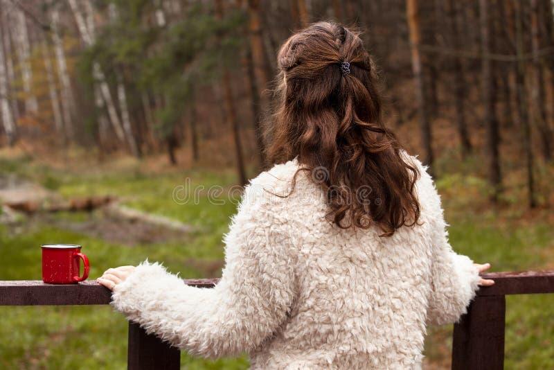 L'adolescente de fille dans un manteau de fourrure blanc se tient sur un pont en bois, la tournant de nouveau à l'appareil-photo, photographie stock libre de droits