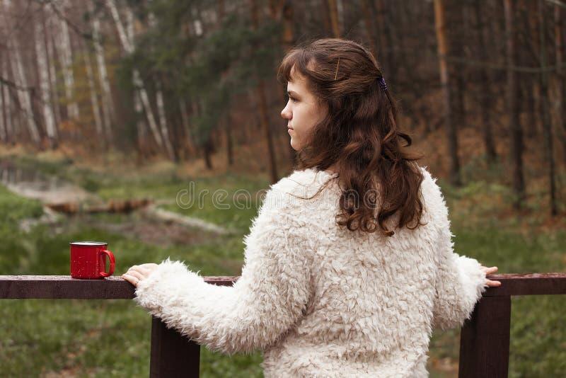L'adolescente de fille dans un manteau de fourrure blanc se tient sur un pont en bois, la tournant de nouveau à l'appareil-photo, images stock