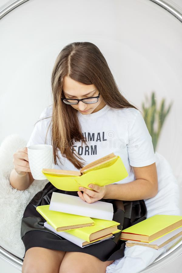 L'adolescente de fille lit avec enthousiasme un livre avec des verres Thé potable Concept d'éducation, passe-temps et étude et jo photos libres de droits