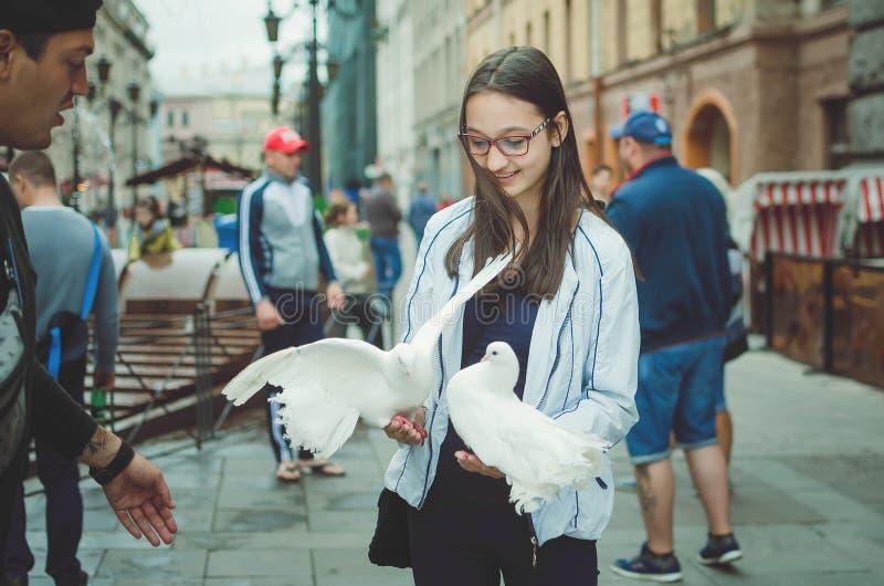 L'adolescente de fille marche sur la rue de St Petersburg, se tient dans les mains des pigeons blancs photo stock