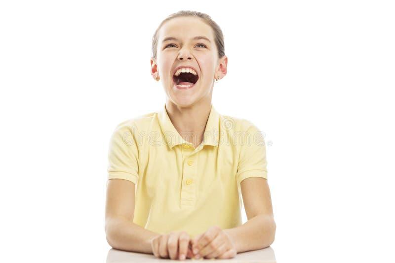 L'adolescente de fille s'assied à la table et aux rires D'isolement sur un fond blanc images libres de droits