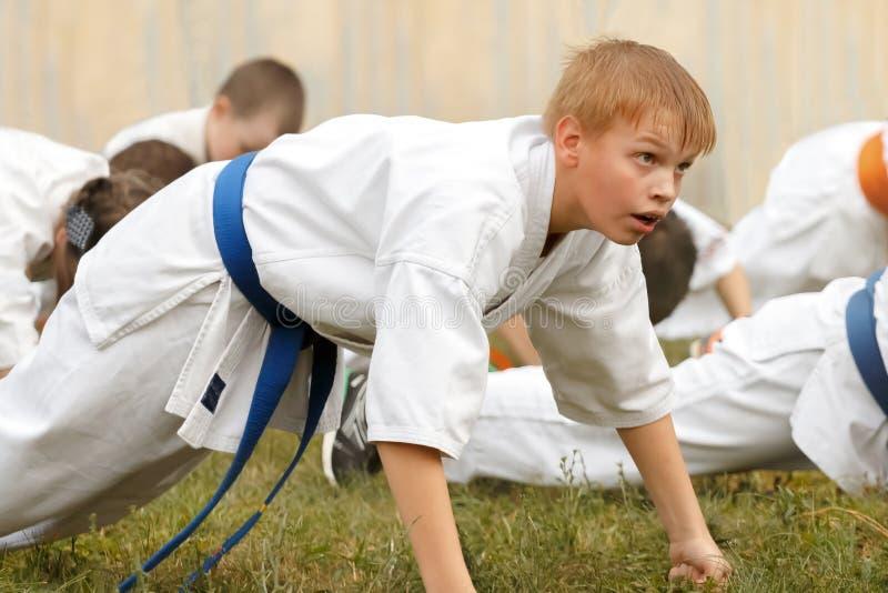 L'adolescente del ragazzo in kimono esegue spinta-UPS sui pugni immagini stock