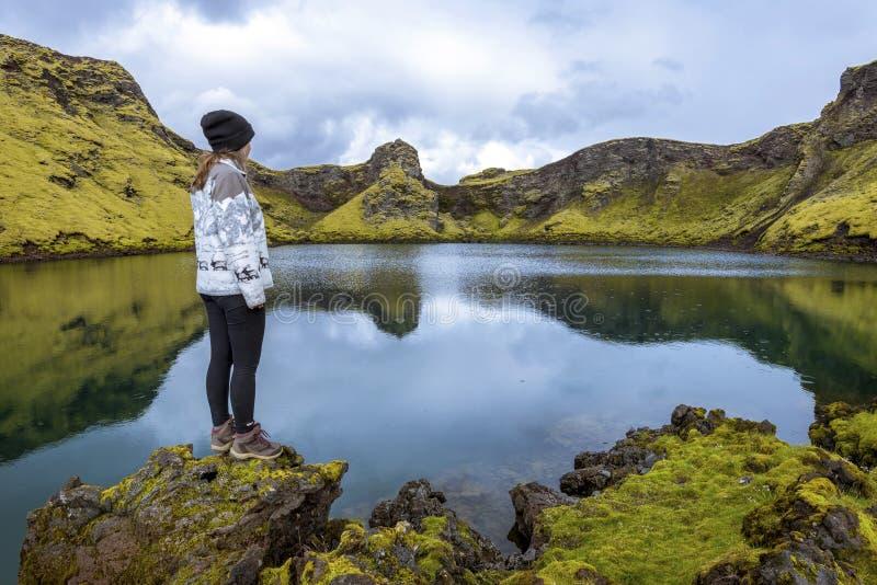 L'adolescente della ragazza sta restando nel confine dello stagno nel cratere Tjarnargigur, uno della maggior parte dei crateri i fotografia stock libera da diritti