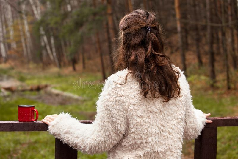 L'adolescente della ragazza in una pelliccia bianca sta su un ponte di legno, girandola di nuovo alla macchina fotografica, esami fotografia stock libera da diritti