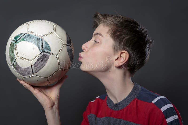 L'adolescente divertente sta baciando un pallone da calcio fotografie stock libere da diritti