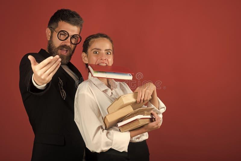 L'adolescente e l'istitutore con i vetri tengono il mucchio dei libri e del libro in denti Di nuovo al concetto del banco Ragazza fotografie stock libere da diritti