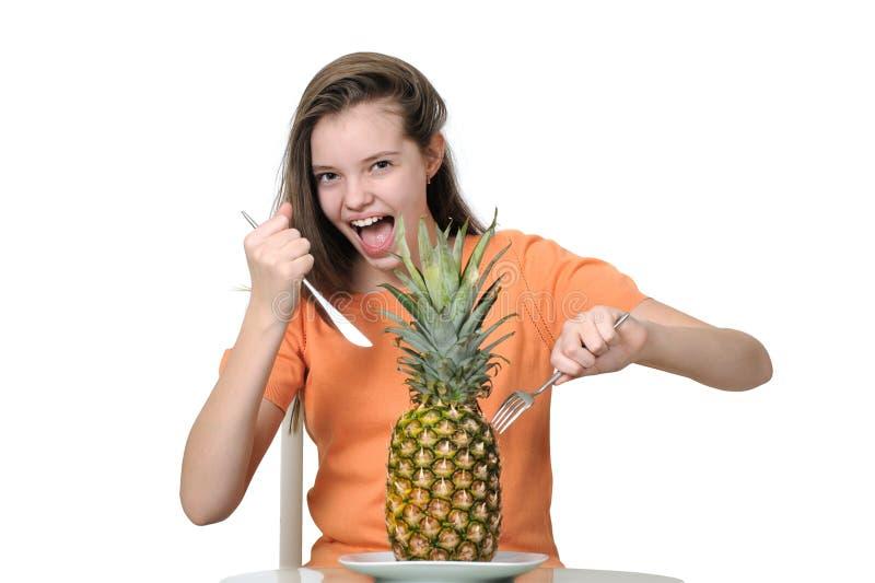 L'adolescente espressivo attacca un coltello e una forcella in un ananas fotografia stock