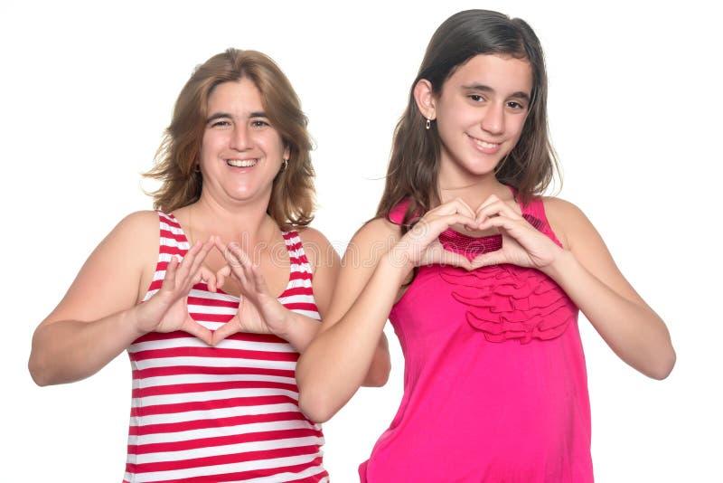 L'adolescente et sa mère faisant le coeur signent photos stock
