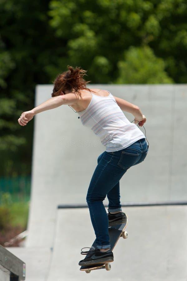 L'adolescente exécute le saut tout en pratiquant faire de la planche à roulettes au pair photographie stock libre de droits