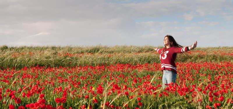 L'adolescente felice che sta in un campo rosso del papavero fiorisce fotografie stock