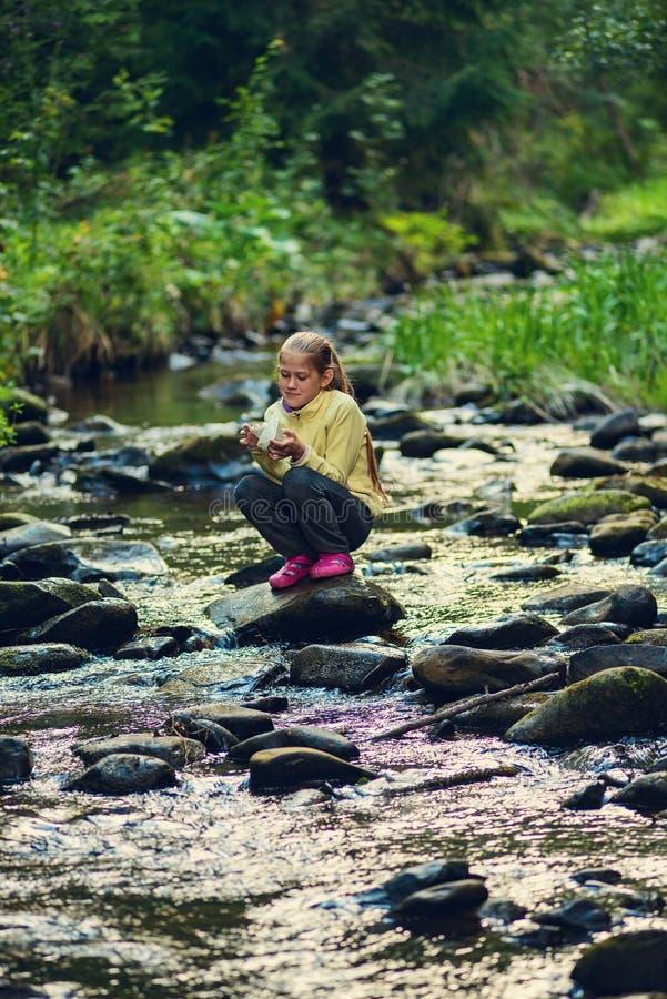L'adolescente felice si siede su una roccia in mezzo ad un ri della montagna fotografia stock
