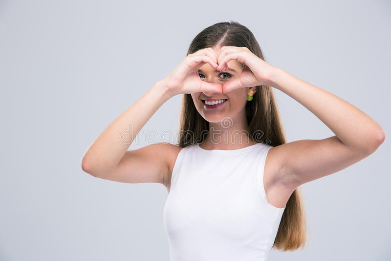 L'adolescente femminile sorridente che mostra il cuore gesture con le dita fotografie stock libere da diritti